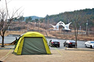 고성 상족암군립공원 무료주차장 쪽에 공원과 캠핑장이 조성됐다. 공룡 모형이 서 있다.<사진:이윤정 기자>